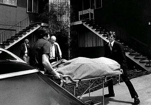 The body of Kemper's last victim is removed from his house by policemen.